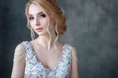 Bride blonde woman in a modern color wedding dress with elegant hair style and make up. Fashion beauty portrait. Over textured background royalty free stock photos