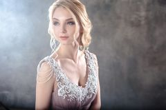 Bride blonde woman in a modern color wedding dress with elegant hair style and make up. Fashion beauty portrait. Over textured background royalty free stock photography