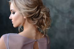 Bride blonde woman in a modern color wedding dress with elegant hair style and make up. Fashion beauty portrait. Over textured background royalty free stock images