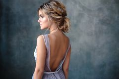 Bride blonde woman in a modern color wedding dress with elegant hair style and make up. Fashion beauty portrait. Over textured background royalty free stock image