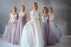 Bride blonde young women in a modern color wedding dress with elegant hair style and make up. Fashion beauty portrait composition. Over textured background stock photos