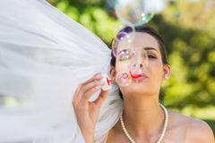 Bride blowing soap bubbles in park Royalty Free Stock Photography
