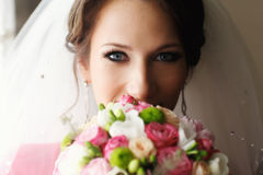 Bride with blue eyes looks above the bouquet Stock Images