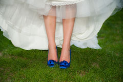 Bride With Blue High Heel Shoes. A bride showing off her'something blue' tradition by wearing blue shoes under her wedding gown while standing on green grass stock photos