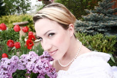 Bride and Boquet. Bride holds her boquet of Lilacs up to smell Royalty Free Stock Image