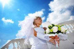 Bride with the bouqet. A young beautiful bride against bright blue sky Royalty Free Stock Photo