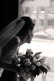 Bride with a bouquet. The bride with a bouquet looks out a door. b/w+sepia royalty free stock image