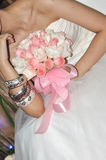 Bride and bouquet. A bride is holding a bouquet, with bracelet around her arm Stock Images