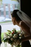 Bride with a bouquet. The bride with a bouquet looks out a door stock photography
