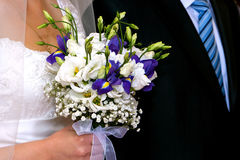 Bride bouquet. Bride with  bouquet  with white  and blue flowers near groom with black suit and blue tail detail Stock Photography