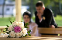 Bride bouquet. With red magenta and white roses with out of focus bride and groom looking Stock Photos