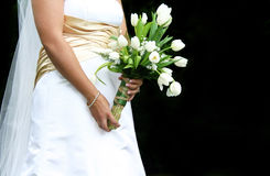 Bride with Bouquet. Bride in wedding dress holding bouquet of tulips with black background Stock Photography