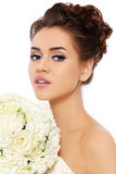 Bride with bouquet. Portrait of beautiful bride with stylish make-up and hairdo holding bouquet in her hands, over white background stock photography