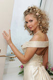 Bride with bouquet. A bride having a reflective moment by some curtains in her room after her marriage Royalty Free Stock Photography