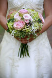 Bride with Bouquet. Bride in a white dress holding a beautiful bouquet of roses Royalty Free Stock Photos