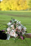 Bride bouquet and autumn leaves. The bride and groom hold the bouquet in fron of the colorful autumn forest royalty free stock photos