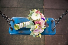 Bride bouquet on blue swing. With chains Stock Images