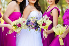 Bride with a bouquet and the bridesmaids Stock Photos