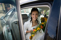 Bride with bouquet in car Stock Photography
