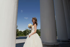 The bride with a bouquet at columns. The bride in a wedding dress with a bouquet near to columns Royalty Free Stock Photos