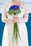 Bride with bouquet of flowers. Bride in white dress holds bouquet with blue  flowers Stock Images