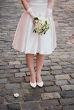 Bride with a bouquet of flowers. Bride on the road with a bouquet of flowers without the face Royalty Free Stock Images