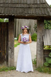 The bride with a bouquet of flowers posing in the photo on the nature. Beauty bride in bridal gown with bouquet and lace veil on the nature. Beautiful model girl Royalty Free Stock Photography
