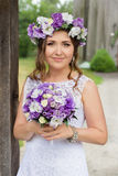 The bride with a bouquet of flowers posing in the photo on the nature. Beauty bride in bridal gown with bouquet and lace veil on the nature. Beautiful model girl Stock Photography