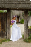 The bride with a bouquet of flowers posing in the photo on the nature. Beauty bride in bridal gown with bouquet and lace veil on the nature. Beautiful model girl Royalty Free Stock Photo
