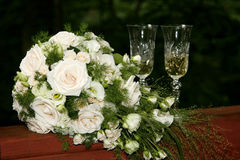 Bride bouquet and glasses. Two glasses of champagne compliment the bouquet nicely Royalty Free Stock Photo