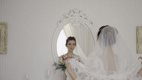 Bride with a bouquet goes to the mirror stock video footage