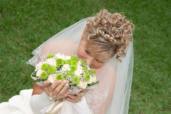 The bride with a bouquet on the green grass Royalty Free Stock Photos