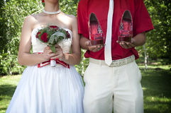 Bride with a bouquet and groom with the shoes Stock Image