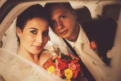 Bride with bouquet and groom sitting in car Stock Images