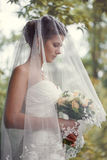 Bride with a bouquet in the hand. Is worth in the alley Royalty Free Stock Photography