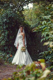 Bride with a bouquet in the hand. Is worth in the alley Royalty Free Stock Photos