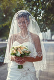 Bride with a bouquet in the hand. Is worth in the alley Royalty Free Stock Photo