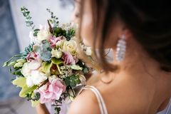 Bride with bouquet in hands, frame from behind shoulder. The background is blurred Stock Photos