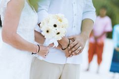 Bride and bouquet hold hand with groom at wedding ceremony stock photos