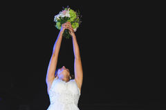 Bride with Bouquet. Bride holding wedding bouquet up at night Stock Photo