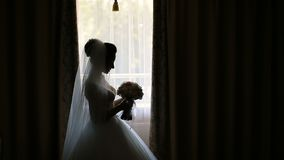 Bride with Bouquet. Bride holds wedding bouquet before window, silhouette indoor view stock video