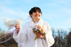 Bride with bouquet holds white dove. Smiling bride with bouquet holds white dove and looks into distance at winter outdoors stock images