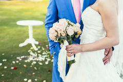 Bride with bouquet of pink flowers and groom in blue suit togeth Stock Images