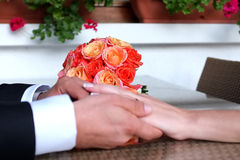 Bride Bouquet. Red flowers bride bouquet with bride and groom hands holding each other Stock Images