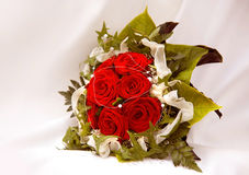 Bride bouquet. A bride bouquet with red rose flowers in light textile ambiance Royalty Free Stock Photo
