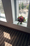 Bride bouquet of red roses before the wedding stands on the window overlooking the street of the city. Bride bouquet of red roses before the wedding, stands on Royalty Free Stock Photography