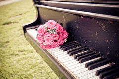 Bride bouquet. A rose bouquet on a vintage piano Royalty Free Stock Image