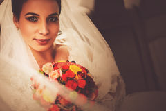 Bride with bouquet of roses sitting in car Royalty Free Stock Images
