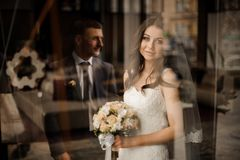 Bride with bouquet of roses smiling and waiting for groom. Beautiful brunette bride in a dress and with bouquet of roses smiling and waiting for her stylish stock photos