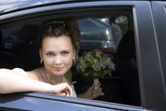 Bride with bouquet sitting in wedding car Royalty Free Stock Photo